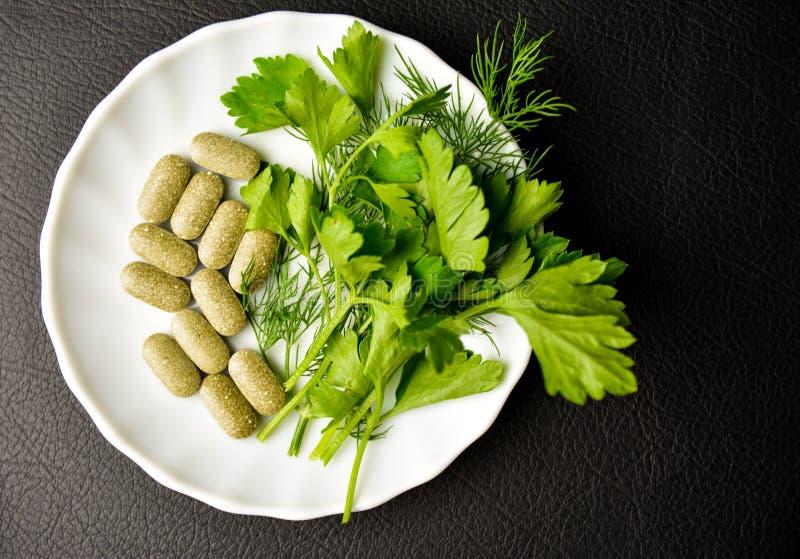 Υγιή τρόφιμα, εναλλακτικά τρόφιμα, μαϊντανός στα φύλλα και τις ταμπλέτες σε ένα άσπρο πιάτο στοκ εικόνες με δικαίωμα ελεύθερης χρήσης