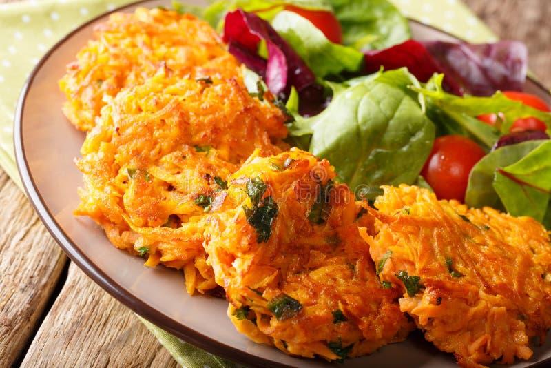 Υγιή τρόφιμα: εύγευστες τηγανίτες γλυκών πατατών και φρέσκο CL σαλάτας στοκ φωτογραφία με δικαίωμα ελεύθερης χρήσης