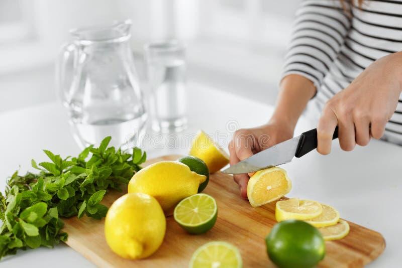 Υγιή τρόφιμα και κατανάλωση Κινηματογράφηση σε πρώτο πλάνο των τεμνόντων λεμονιών κουζινών γυναικών στοκ εικόνες