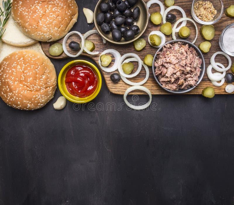 Υγιή τρόφιμα, μαγείρεμα και χορτοφάγο burger τόνου έννοιας με τα τουρσιά και τις ελιές που κόβουν τον πίνακα στο ξύλινο αγροτικό  στοκ φωτογραφίες