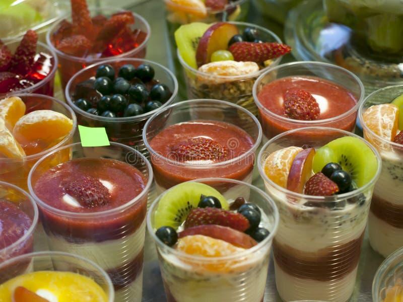 Υγιή τρόφιμα στην επίδειξη, ώριμα φρούτα και γιαούρτι, μικρές μερίδες στα φλυτζάνια στοκ φωτογραφία