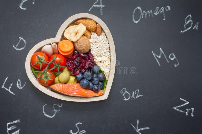 Υγιή τρόφιμα στην καρδιά και χημικά στοιχεία στον πίνακα στοκ φωτογραφία