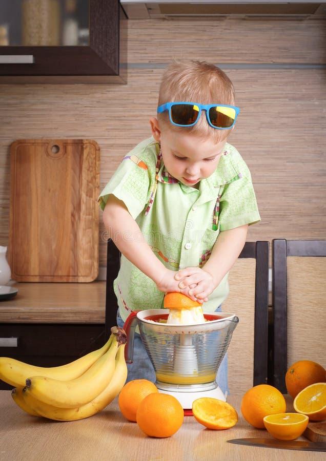 Υγιή τρόφιμα: το αγόρι κάνει το φρέσκο χυμό από πορτοκάλι στοκ φωτογραφία