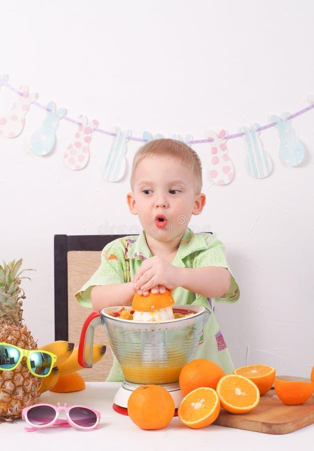 Υγιή τρόφιμα: το αγόρι κάνει το φρέσκο χυμό από πορτοκάλι στοκ φωτογραφίες