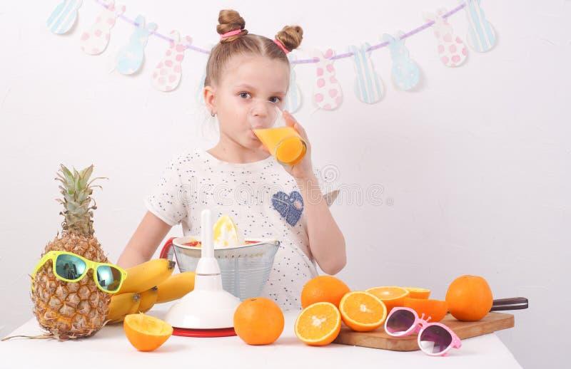 Υγιή τρόφιμα: Το κορίτσι πίνει το φρέσκο χυμό από πορτοκάλι στοκ φωτογραφία