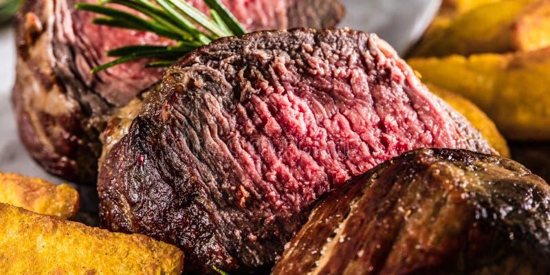 Υγιή ψημένα στη σχάρα μέσος-σπάνια μπριζόλα και λαχανικά βόειου κρέατος με τις ψημένες πατάτες στοκ φωτογραφία