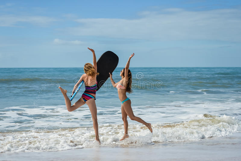Υγιείς αθλητικοί φίλοι κοριτσιών surfer με τους κατάλληλους οργανισμούς που κρατούν τα bodyboards στοκ εικόνα