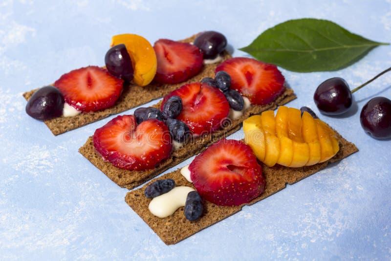 Υγιείς και νόστιμες φρυγανιές με το τυρί, τα φρούτα και τα μούρα στάρπης σε ένα μπλε υπόβαθρο στοκ εικόνες