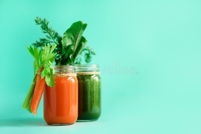 Υγιείς οργανικοί πράσινοι και πορτοκαλιοί καταφερτζήδες στο μπλε υπόβαθρο Ποτά Detox στο βάζο γυαλιού από τα λαχανικά - καρότο στοκ φωτογραφία με δικαίωμα ελεύθερης χρήσης