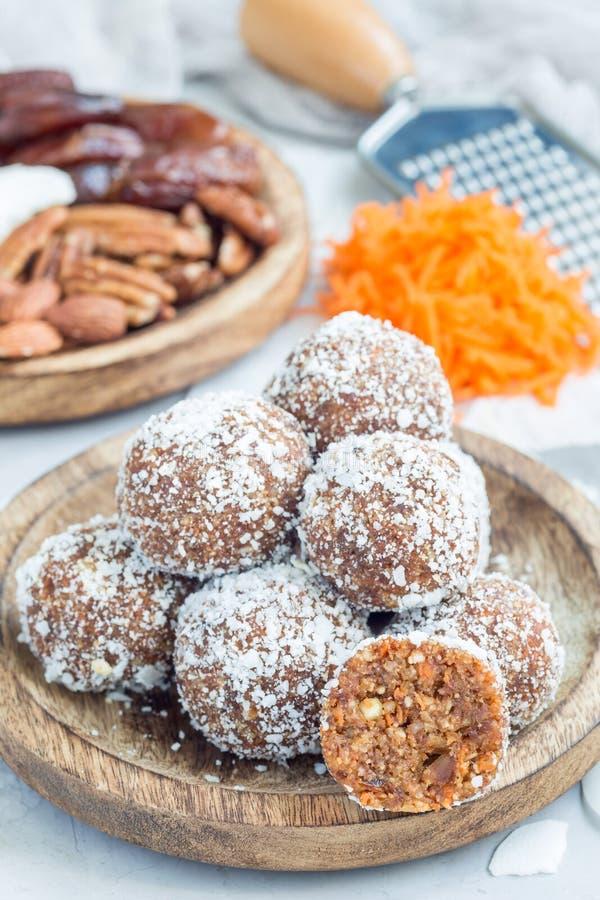 Υγιείς σπιτικές ενεργειακές σφαίρες paleo με το καρότο, τα καρύδια, τις ημερομηνίες και τις νιφάδες καρύδων, στο ξύλινο πιάτο στοκ εικόνες