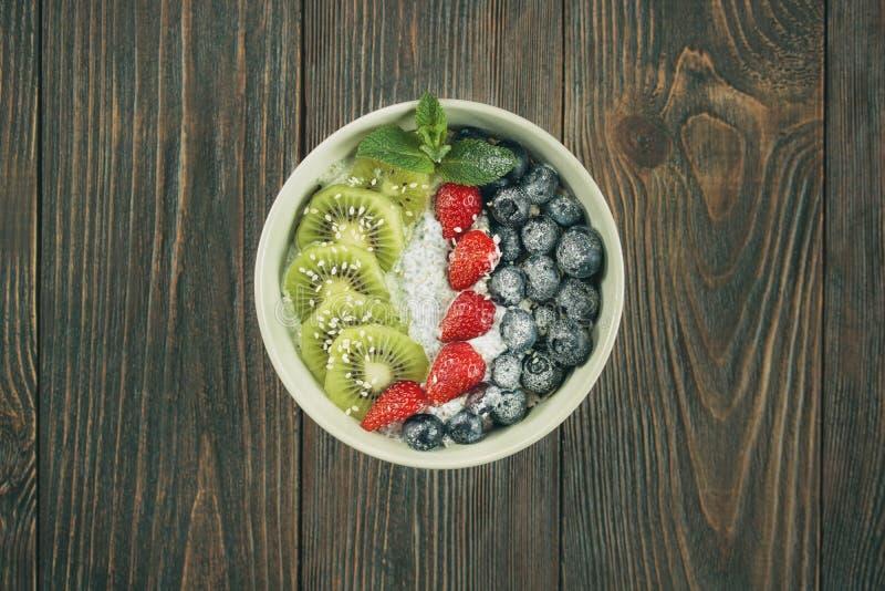 Υγιείς σπόροι κύπελλων και chia φρούτων με τις φράουλες, τα βακκίνια και το ακτινίδιο στοκ εικόνα
