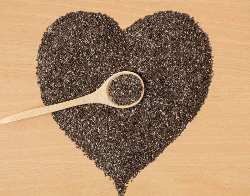 Υγιείς σπόροι Chia υπό μορφή καρδιάς Chia σε ένα ξύλινο κουτάλι σε μια ξύλινη επιτραπέζια κινηματογράφηση σε πρώτο πλάνο στοκ φωτογραφίες με δικαίωμα ελεύθερης χρήσης