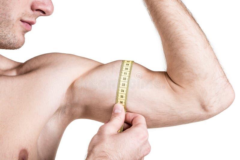 Υγιείς τρόπος ζωής και ικανότητα Όμορφος τύπος αθλητικός, μετρώντας τους μυς, που απομονώνονται στο άσπρο υπόβαθρο Οριζόντιο πλαί στοκ εικόνες