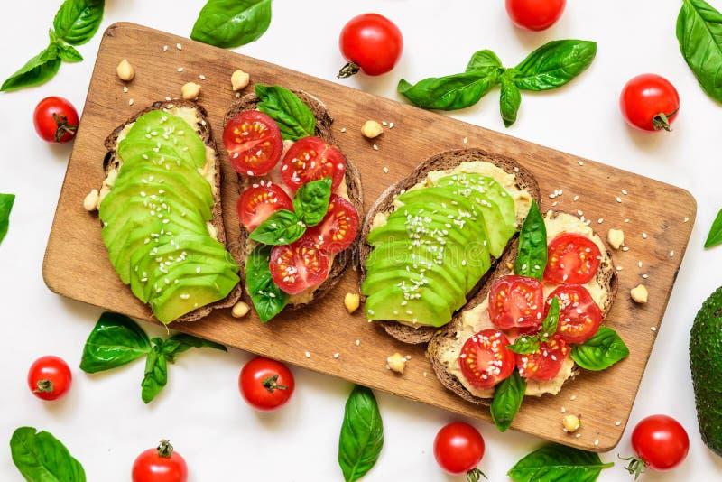 Υγιείς φρυγανιές φρυγανιάς αβοκάντο με το αβοκάντο, τις ντομάτες κερασιών, το βασιλικό και τους σπόρους σουσαμιού στον ξύλινο τέμ στοκ εικόνα