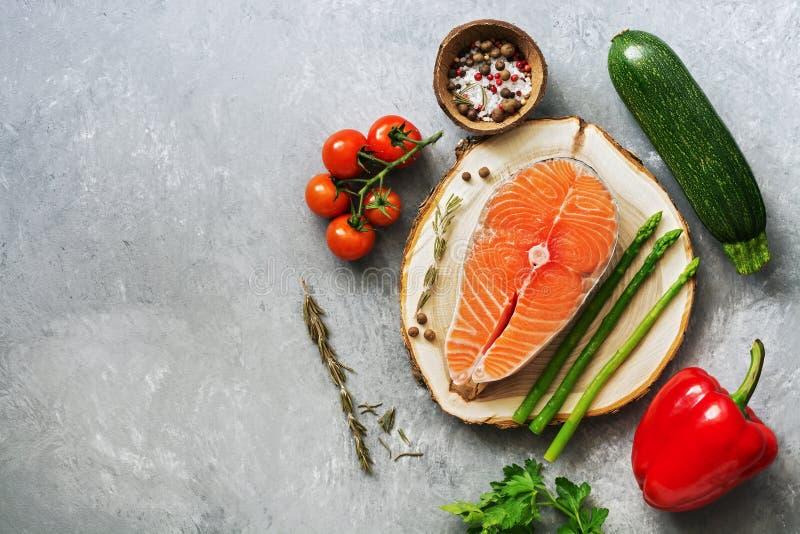 Υγιεινή ισορροπημένη διατροφή, ακατέργαστα ψάρια σολομών και φρέσκα λαχανικά σε ένα γκρίζο υπόβαθρο Υπερυψωμένη άποψη, διάστημα α στοκ εικόνα