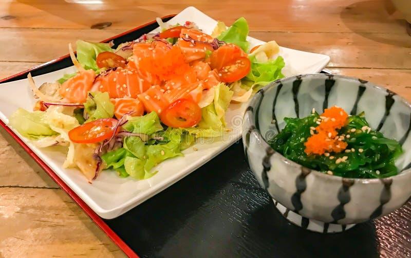 Υγιεινή σολομοσαλάτα με λεμονόχαρτο και ιαπωνική σαλάτα με φύκια σε ξύλινο τραπέζι στο εστιατόριο στοκ εικόνες