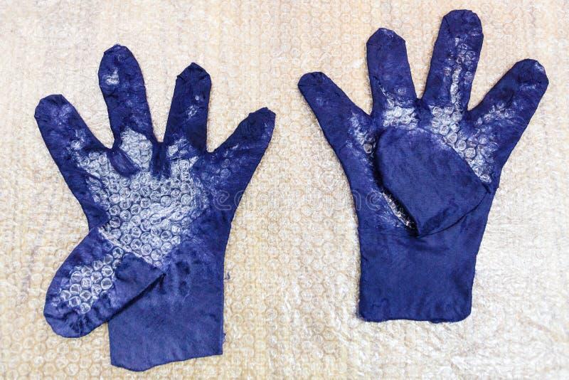Υγρά γάντια με το διαμορφωμένο δάχτυλο και το τέμνον σχέδιο στοκ φωτογραφίες
