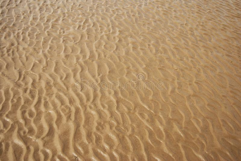 Υγρή σύσταση άμμου Αμμώδης παραλία για το υπόβαθρο καλοκαιρινές διακοπές στοκ φωτογραφία