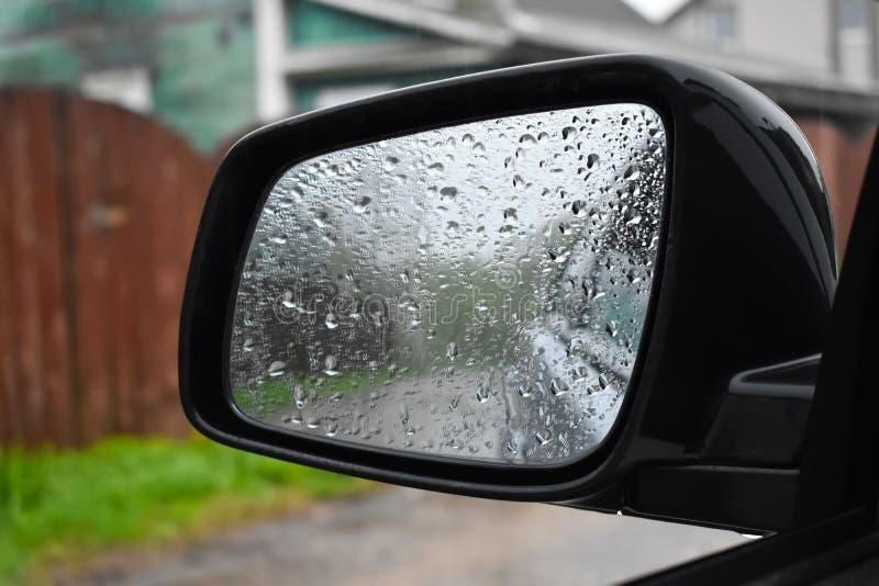 Υγρός από τη βροχή ο καθρέφτης στενού του επάνω αυτοκινήτων στοκ φωτογραφία
