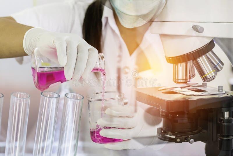 Υγρό ερευνητικής φέρνοντας χημείας γυναικών επιστημόνων με τον εξοπλισμό μικροσκοπίων για τα ερευνητικά πειράματα στο σωλήνα δοκι στοκ φωτογραφία με δικαίωμα ελεύθερης χρήσης