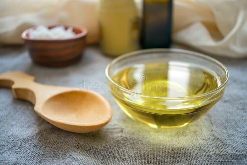 Υγρό πετρέλαιο καρύδων MCT στο στρογγυλό κύπελλο γυαλιού με το ξύλινο κουτάλι και στοκ εικόνα με δικαίωμα ελεύθερης χρήσης