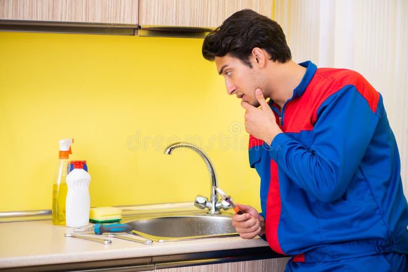 Υδραυλικός που επισκευάζει τη βρύση στην κουζίνα στοκ εικόνα με δικαίωμα ελεύθερης χρήσης