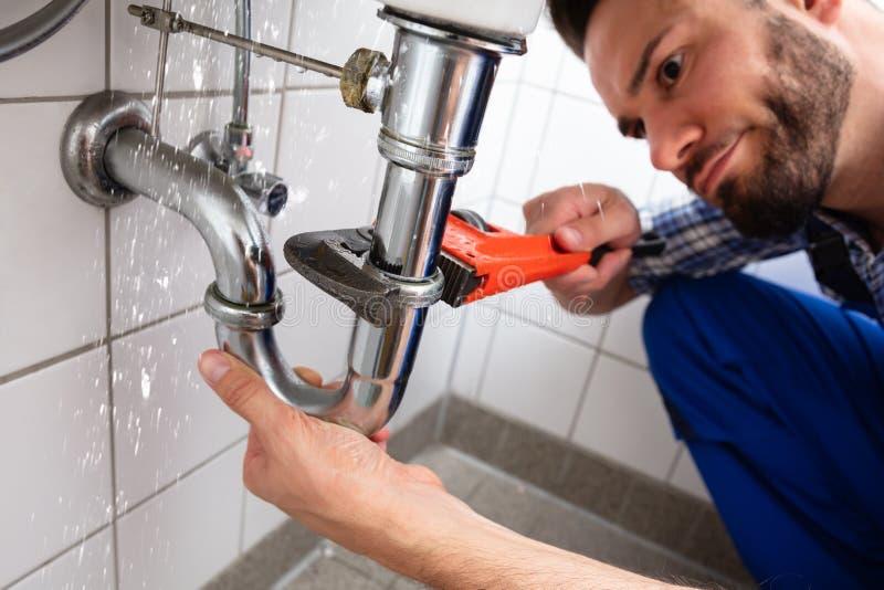 Υδραυλικός που επισκευάζει τη διαρροή σωλήνων νεροχυτών στοκ εικόνα