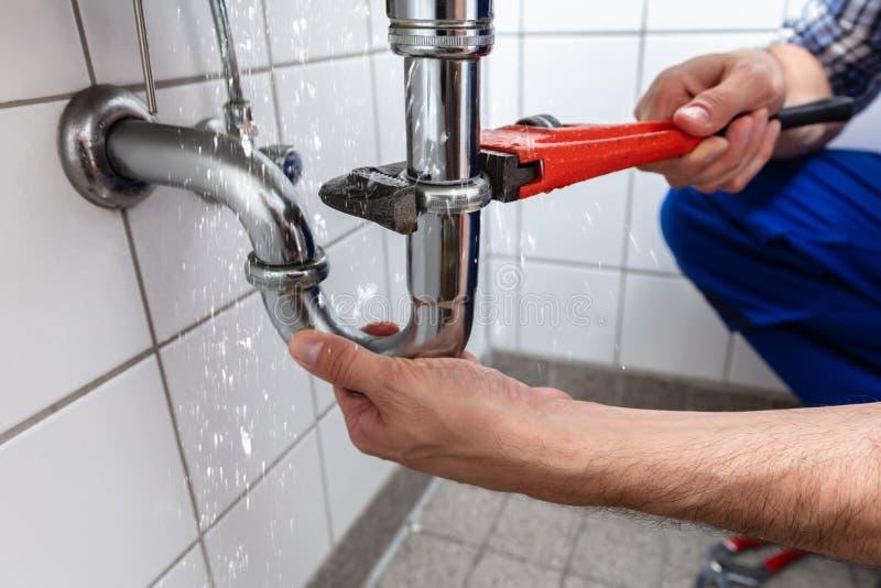 Υδραυλικός που επισκευάζει τη διαρροή σωλήνων νεροχυτών στοκ φωτογραφία με δικαίωμα ελεύθερης χρήσης