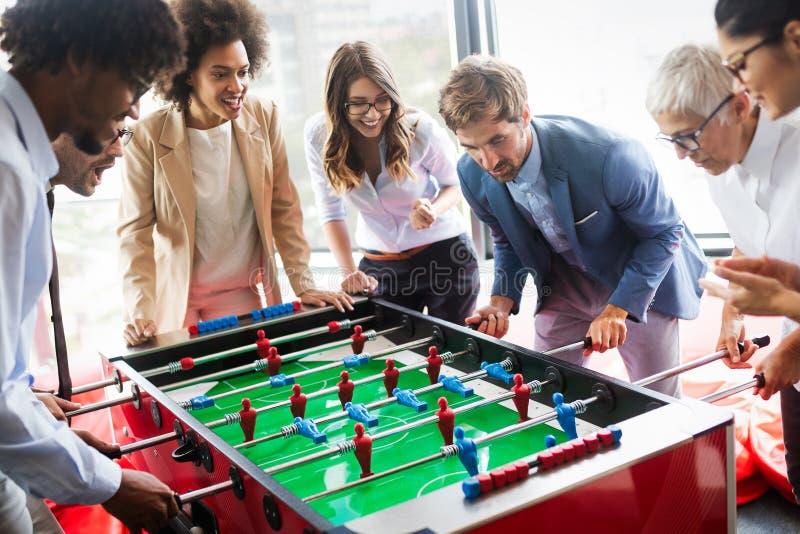 Υπάλληλοι που παίζουν το εσωτερικό παιχνίδι επιτραπέζιου ποδοσφαίρου στο γραφείο κατά τη διάρκεια του χρόνου σπασιμάτων στοκ φωτογραφία
