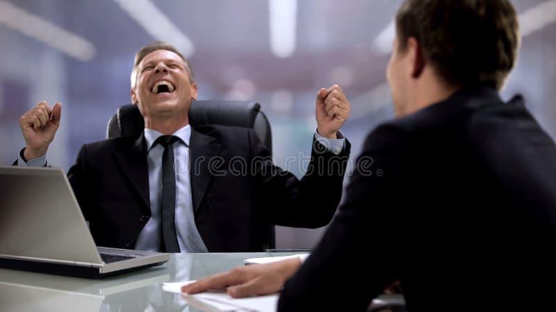 Υπάλληλος και εργοδότης γελά δυνατά, λέγοντας αστεία στη δουλειά στο γραφείο, διασκέδαση στοκ εικόνες