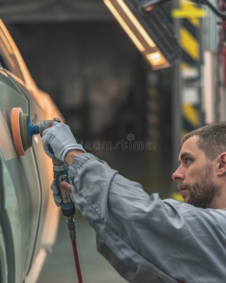 Υπάλληλος στο κατάστημα που χρωματίζει τα χρωματισμένα στιλβωτικές ουσίες μέλη του σώματος σωμάτων αυτοκινήτων στοκ εικόνα