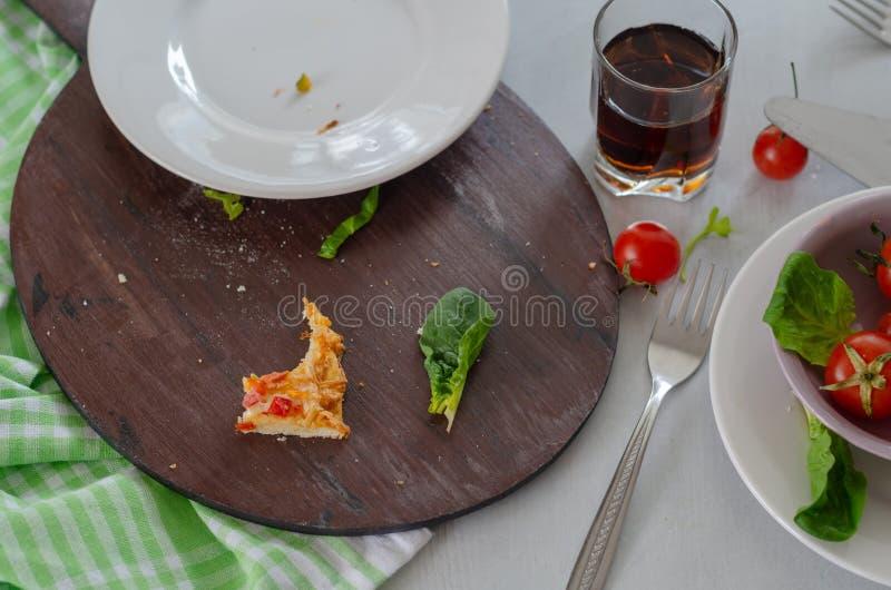Υπάρχουν υπολείμματα της πίτσας και του βρώμικου πιάτου στον πίνακα στοκ φωτογραφίες