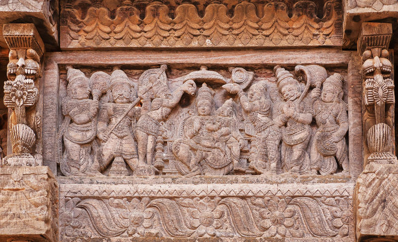 Υπάλληλοι και θαυμαστές του ινδικού Θεού στο χαρασμένο ξύλινο τοίχο του παραδοσιακού ινδού ναού στοκ φωτογραφίες