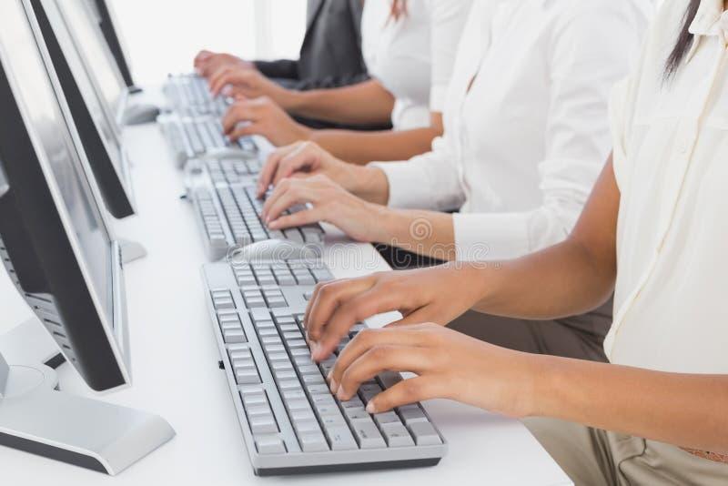 Υπάλληλοι που δακτυλογραφούν στους υπολογιστές τους στοκ εικόνα με δικαίωμα ελεύθερης χρήσης