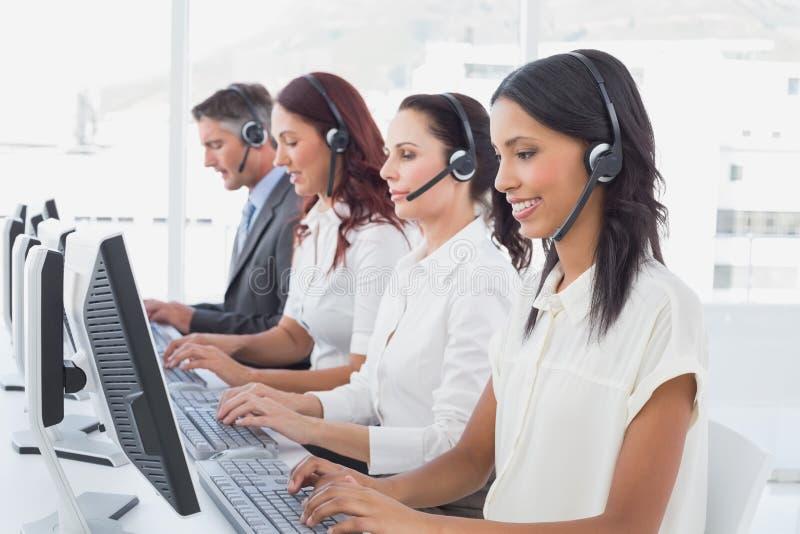Υπάλληλοι που δακτυλογραφούν στους υπολογιστές τους στοκ φωτογραφία