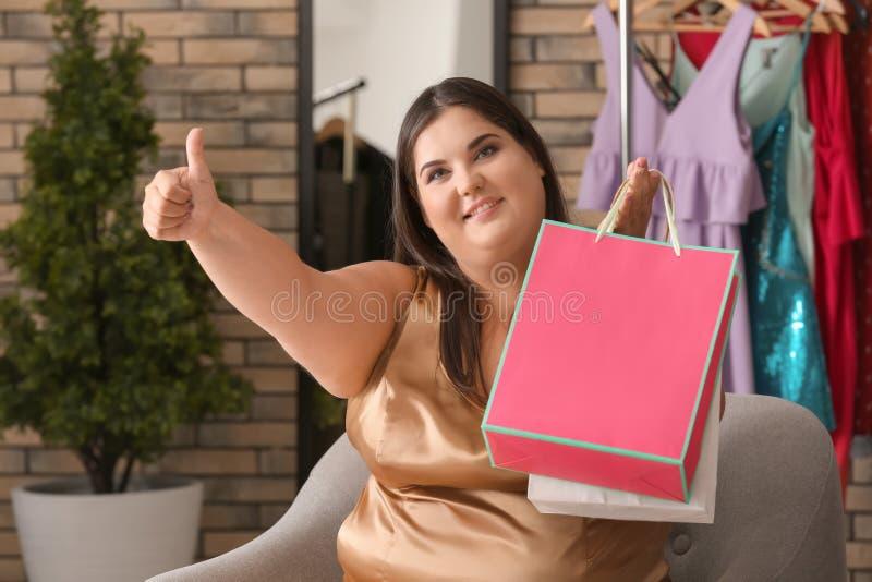 Υπέρβαρη γυναίκα με τις τσάντες αγορών που παρουσιάζουν αντίχειρας-επάνω στη χειρονομία στο κατάστημα ιματισμού στοκ εικόνες με δικαίωμα ελεύθερης χρήσης