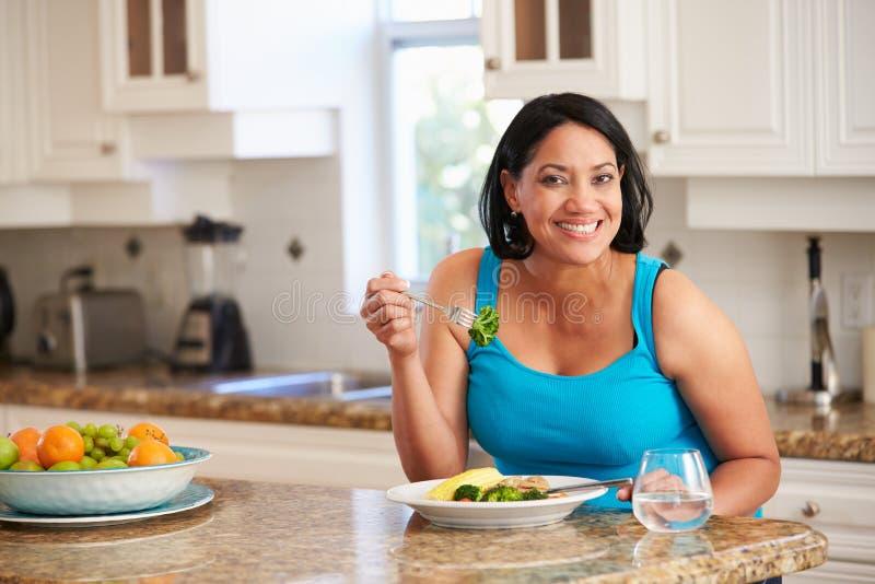 Υπέρβαρη γυναίκα που τρώει το υγιές γεύμα στην κουζίνα στοκ εικόνες