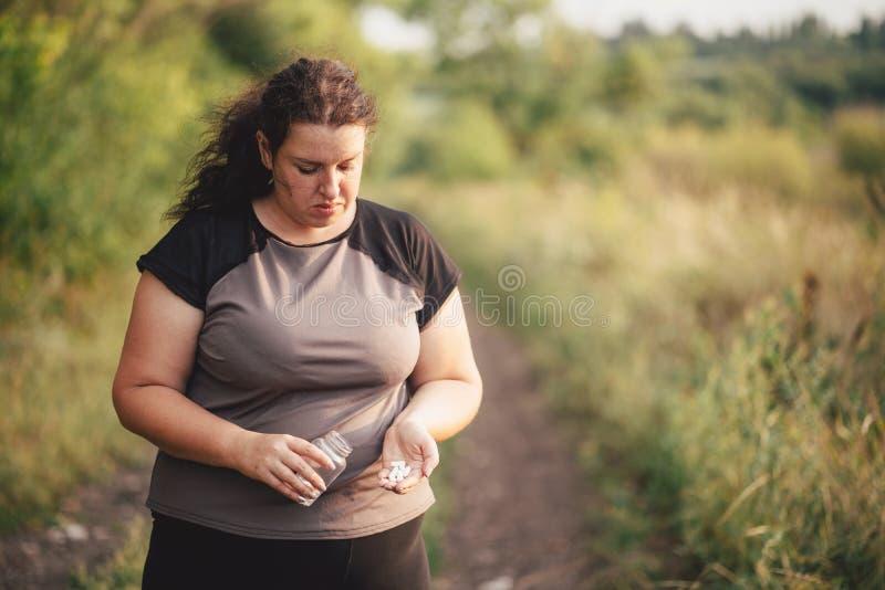 Υπέρβαρη παχιά γυναίκα με ένα μπουκάλι των χαπιών διατροφής στοκ εικόνα