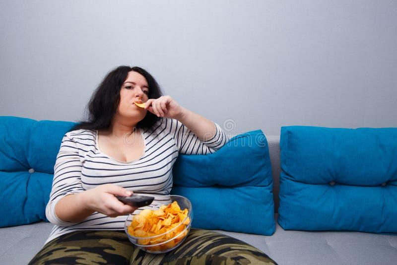 Υπέρβαρη συνεδρίαση γυναικών πατατών καναπέδων στον καναπέ, που τρώει τα τσιπ στοκ φωτογραφία