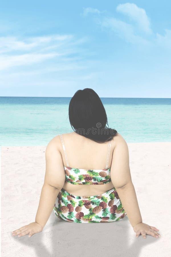 Υπέρβαρη χαλάρωση γυναικών στην παραλία στοκ φωτογραφία