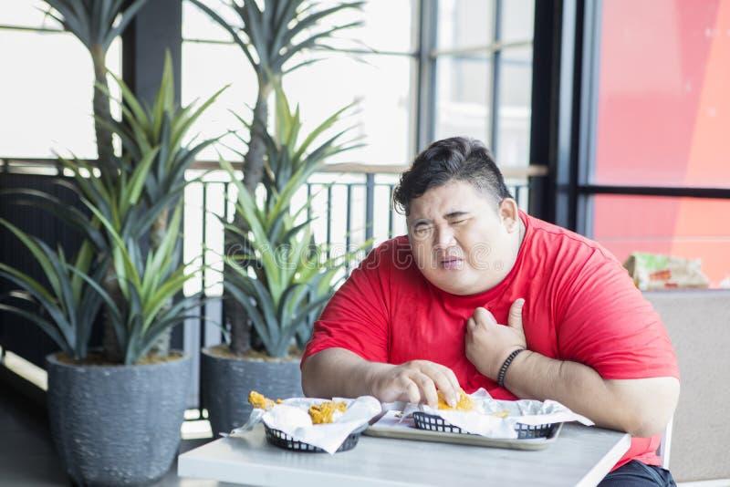 Υπέρβαρος άνδρας παθαίνει καρδιακή προσβολή στο εστιατόριο στοκ εικόνες με δικαίωμα ελεύθερης χρήσης