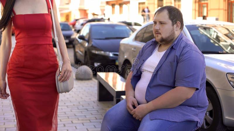 Υπέρβαρος άνδρας που εξετάζει την κομψή γυναίκα, διαφορά τρόπου ζωής, κίνητρο στοκ εικόνες