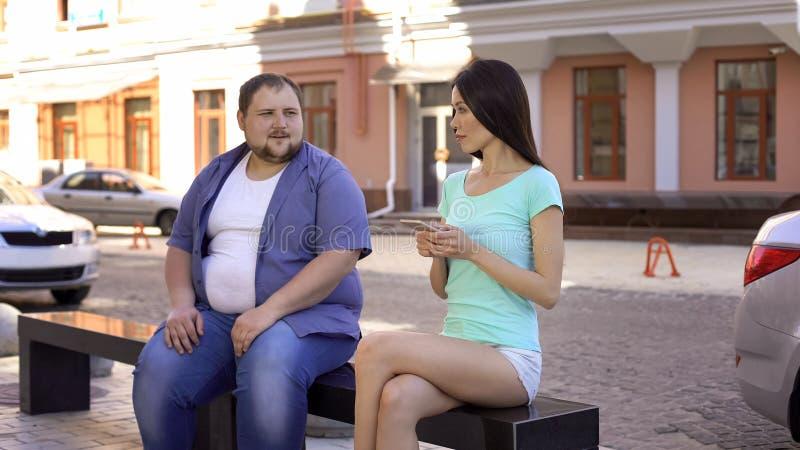 Υπέρβαρο αρσενικό που προσπαθεί να εξοικειωθεί με το φίλαθλο νέο θηλυκό στον πάγκο στοκ εικόνα