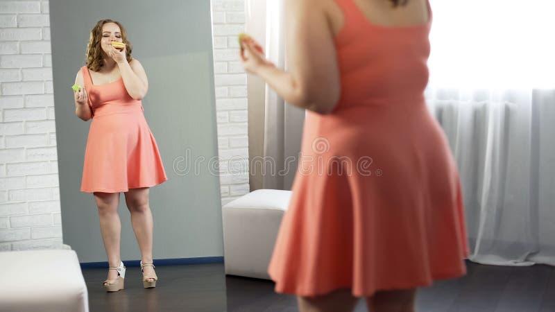 Υπέρβαρο θηλυκό που τρώει τα γλυκά donuts μπροστά από τον καθρέφτη που ικανοποιεί με το βλέμμα της στοκ εικόνες
