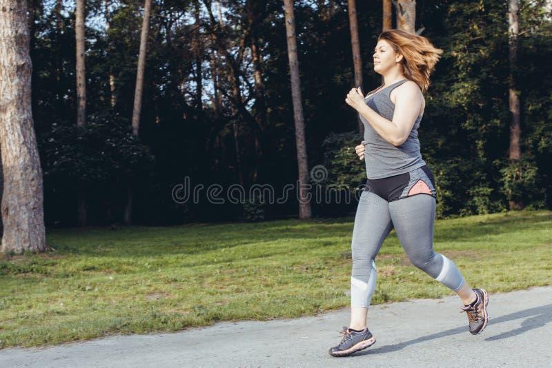 Υπέρβαρο τρέξιμο γυναικών όμορφη απώλεια έννοιας κοιλιών πέρα από τη λευκή γυναίκα βάρους στοκ φωτογραφία