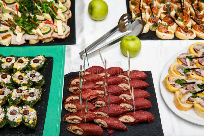 Υπέροχα διακοσμημένος εξυπηρετώντας τον πίνακα συμποσίου με τα διαφορετικά πρόχειρα φαγητά και τα ορεκτικά τροφίμων στο εταιρικό  στοκ φωτογραφίες