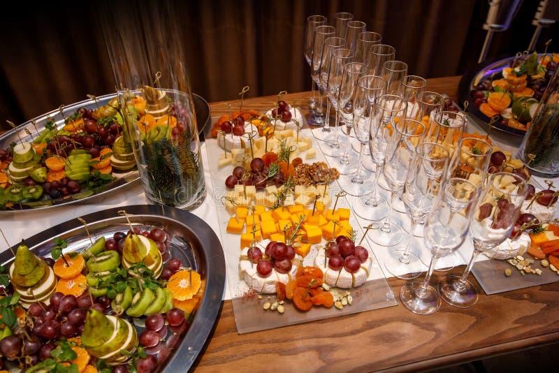 Υπέροχα διακοσμημένος εξυπηρετώντας τον πίνακα συμποσίου με τα διαφορετικά πρόχειρα φαγητά και τα ορεκτικά τροφίμων σε εταιρικό στοκ εικόνες