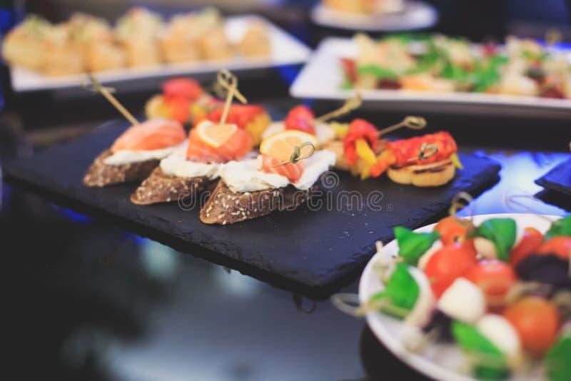 Υπέροχα διακοσμημένος εξυπηρετώντας τον πίνακα συμποσίου με τα διαφορετικά πρόχειρα φαγητά και τα ορεκτικά τροφίμων στοκ εικόνες