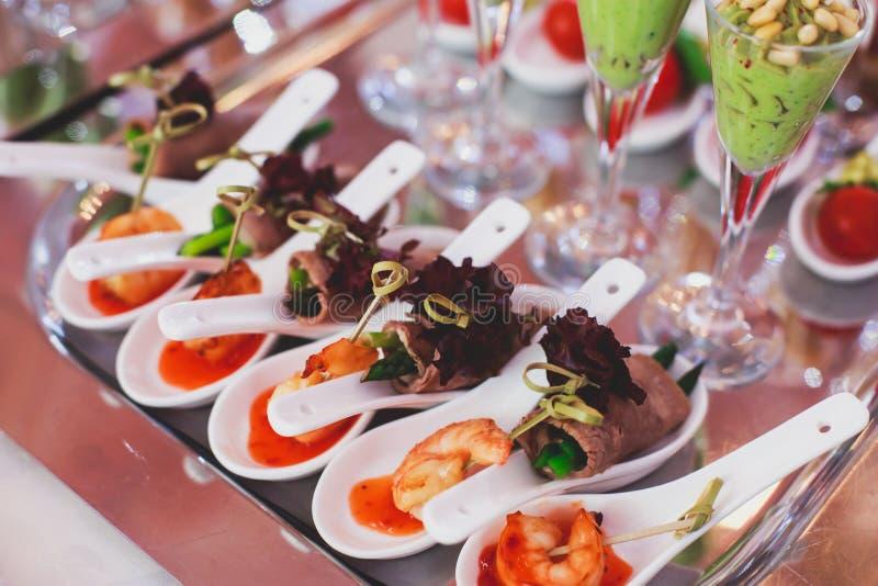 Υπέροχα διακοσμημένος εξυπηρετώντας τον πίνακα συμποσίου με τα διαφορετικά πρόχειρα φαγητά και τα ορεκτικά τροφίμων στο εταιρικό  στοκ εικόνες