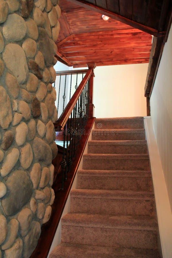 Υπέροχα καλυμμένη με τάπητα σκάλα με τα ξύλινες ανώτατα όρια και την εστία πετρών στοκ εικόνα